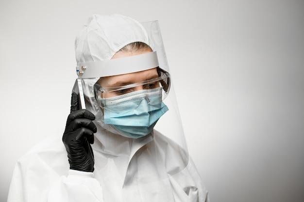 Kobieta lekarz w medycznej odzieży ochronnej i czarnej lateksowej rękawicy trzyma telefon w pobliżu jej ucha