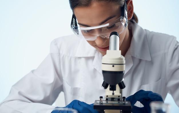 Kobieta lekarz w medycznej sukni i mikroskopem na stole okulary na twarzy badania laboratoryjne