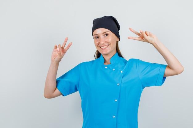 Kobieta lekarz w mundurze pokazując znak zwycięstwa i patrząc wesoło