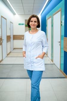 Kobieta lekarz w mundurze stojącym na korytarzu kliniki. profesjonalny lekarz specjalista szpitala, laryngolog lub otolaryngolog, ginekolog lub mammolog