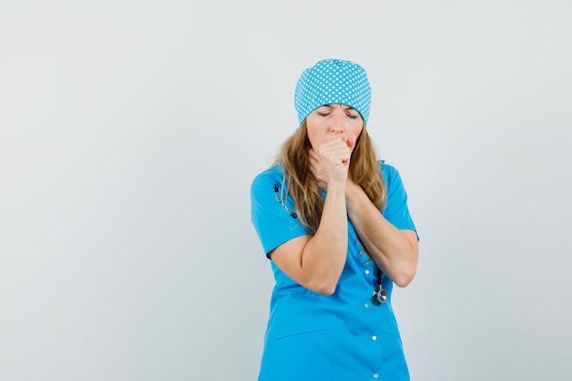 Kobieta lekarz w niebieskim mundurze cierpi na kaszel i wygląda na chorego