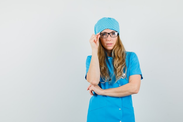 Kobieta lekarz w niebieskim mundurze, dotykając jej okularów i wyglądającej rozsądnie