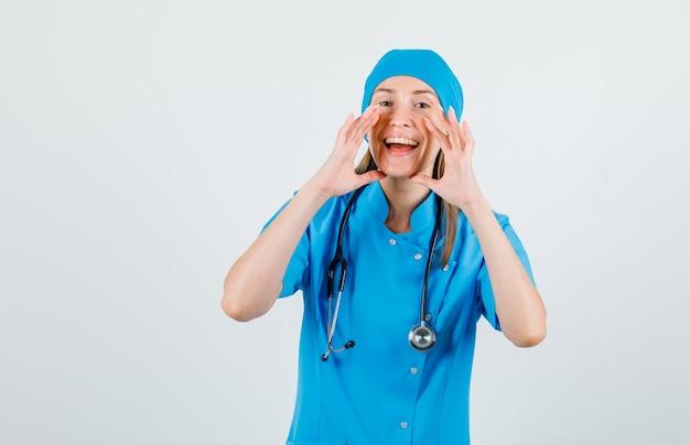 Kobieta lekarz w niebieskim mundurze ogłaszając coś rękami i patrząc na szczęśliwego