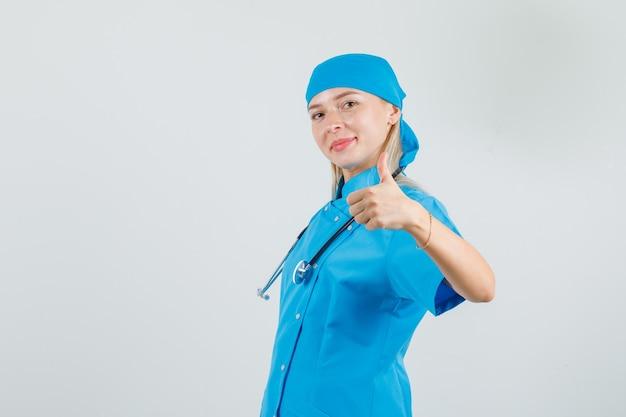 Kobieta lekarz w niebieskim mundurze pokazując kciuk do góry i patrząc wesoło