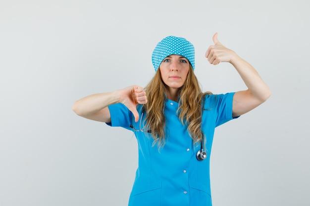 Kobieta lekarz w niebieskim mundurze pokazując kciuk w górę iw dół