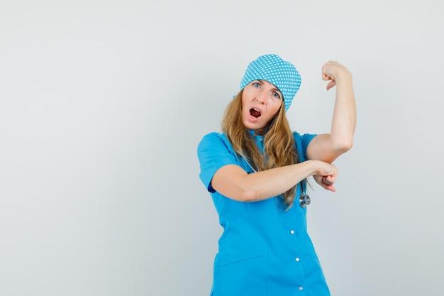 Kobieta lekarz w niebieskim mundurze pokazujący gest sukcesu i wyglądający błogo