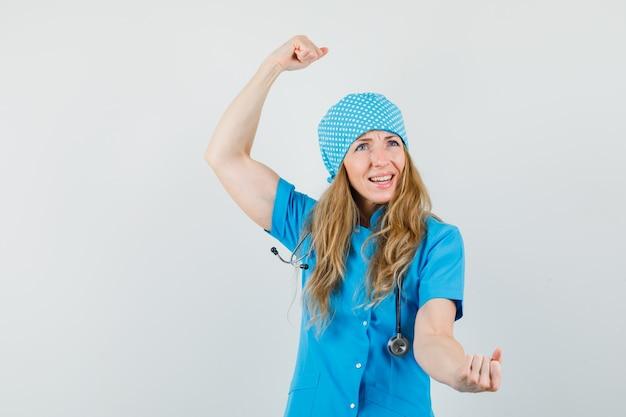 Kobieta lekarz w niebieskim mundurze pokazujący gest zwycięzcy i wyglądający błogo