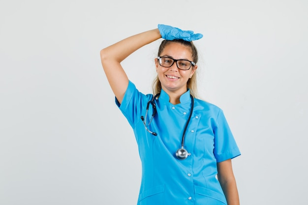 Kobieta lekarz w niebieskim mundurze, rękawiczkach, okularach podnosząc ramię z ręką na głowie i wyglądając wesoło