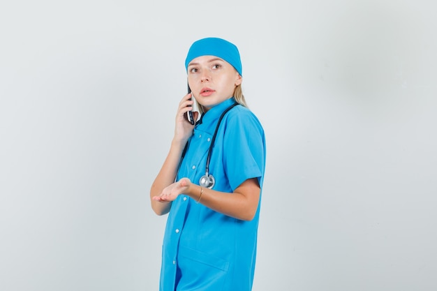 Kobieta lekarz w niebieskim mundurze rozmawia przez telefon komórkowy ze znakiem ręki i patrząc ostrożnie.