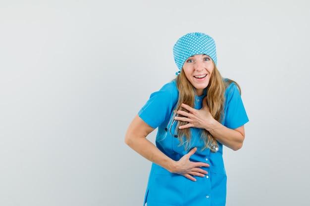 Kobieta lekarz w niebieskim mundurze, śmiejąc się głośno i patrząc na szczęśliwego