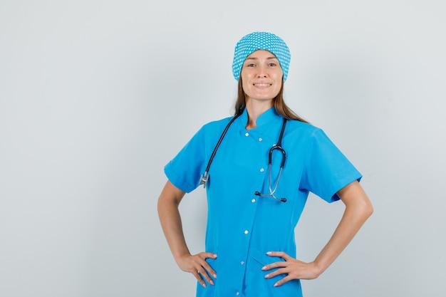 Kobieta lekarz w niebieskim mundurze, stojąc z rękami w talii i patrząc pewnie