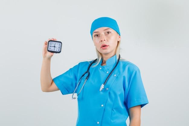 Kobieta lekarz w niebieskim mundurze, trzymając zegar i patrząc punktualny