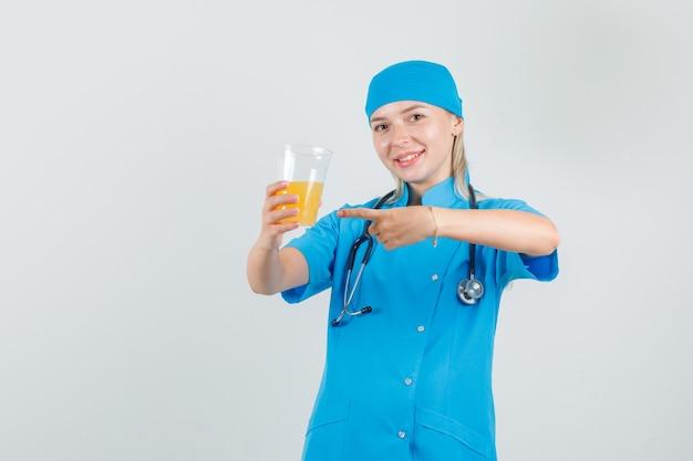 Kobieta lekarz w niebieskim mundurze, wskazując palcem na sok owocowy i patrząc wesoło