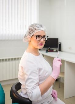 Kobieta lekarz w okularach i białym mundurze siedzi z jednorazową strzykawką na krześle w gabinecie kliniki