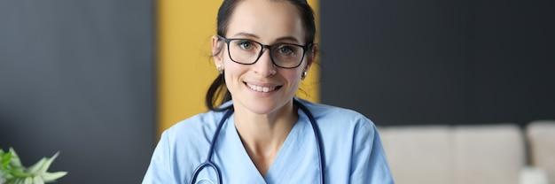 Kobieta lekarz w okularach wypełnia historię medyczną