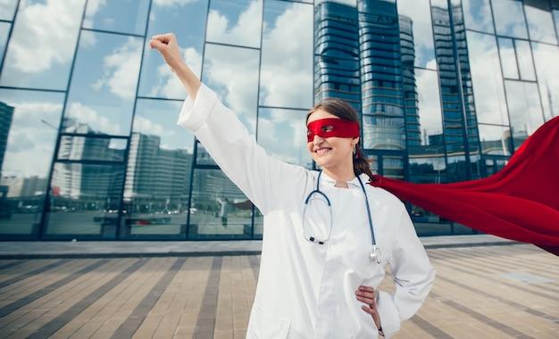 Kobieta lekarz w pelerynie superbohatera jest gotowa do pomocy. zdjęcie z przestrzenią do kopiowania.