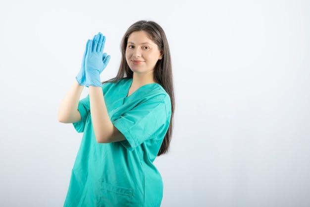 Kobieta lekarz w rękawiczkach medycznych pokazując ręce na białym.