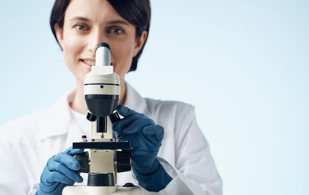 Kobieta lekarz w rękawiczki medyczne i mikroskop na stole profesjonalne laboratorium.