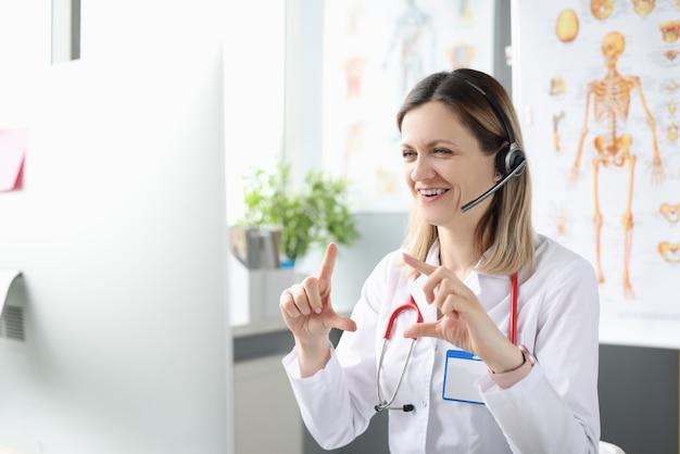 Kobieta lekarz w słuchawkach z mikrofonem udziela konsultacji online