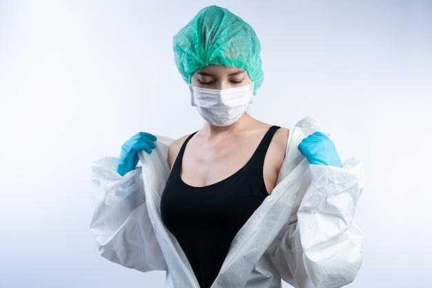 Kobieta lekarz w śoi (osobiste wyposażenie ochronne), zdejmij kombinezon hazmat.