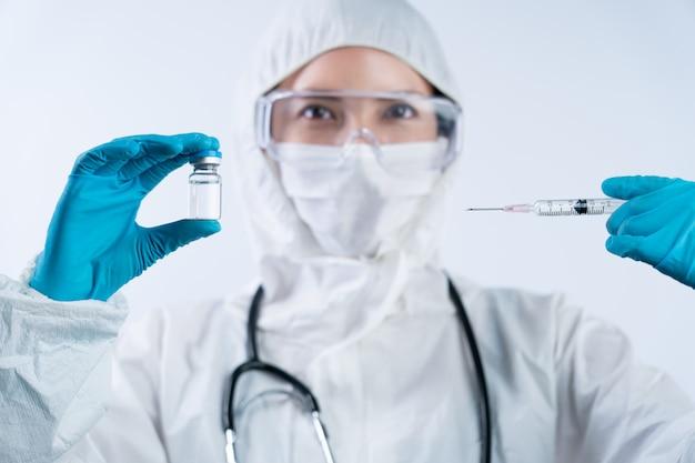 Kobieta lekarz w śoi (środki ochrony indywidualnej), rękawicach, masce na twarz i okularach ochronnych z butelką i igłą ze szczepionką na koronawirusa.
