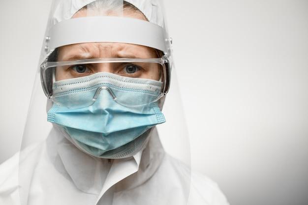 Kobieta lekarz w strój ochronny z tarczą i maska medyczna.