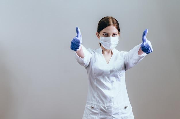 Kobieta lekarz w sukni medycznej iw rękawiczkach medycznych na dłoni pokazuje gest kciuków w górę