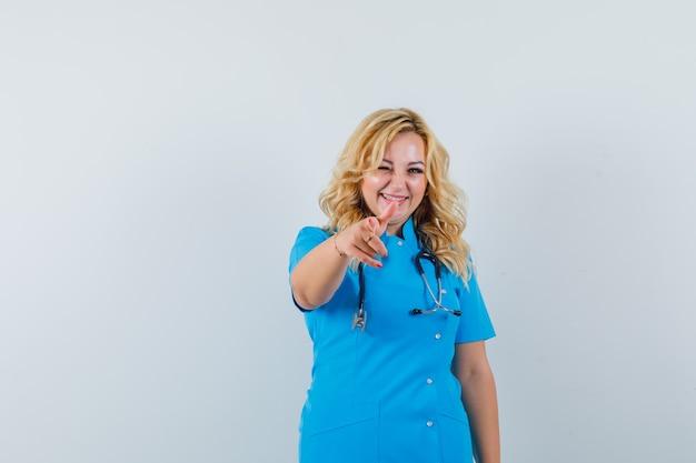 Kobieta lekarz wskazując na aparat, mrugając w niebieskim mundurze i patrząc rozbawiony.