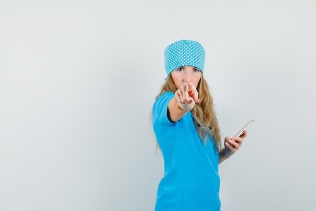 Kobieta lekarz wskazując na aparat trzymając telefon komórkowy w niebieskim mundurze i patrząc surowo