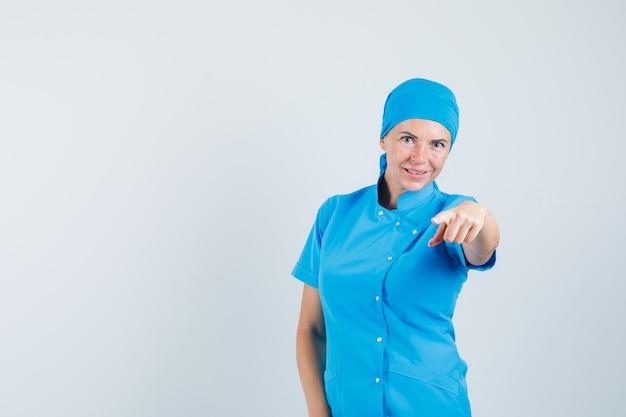 Kobieta lekarz wskazując na aparat w niebieskim mundurze i patrząc pewnie. przedni widok.