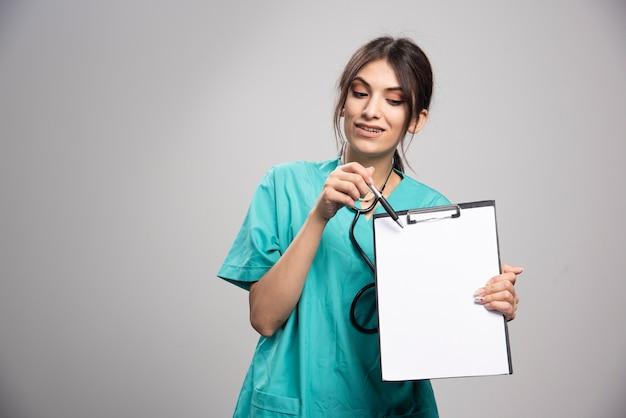 Kobieta lekarz wskazując notatkę w schowku