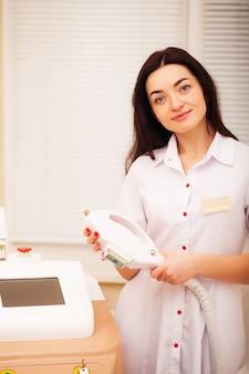 Kobieta lekarz wystawia maszynę do laserowego usuwania włosów