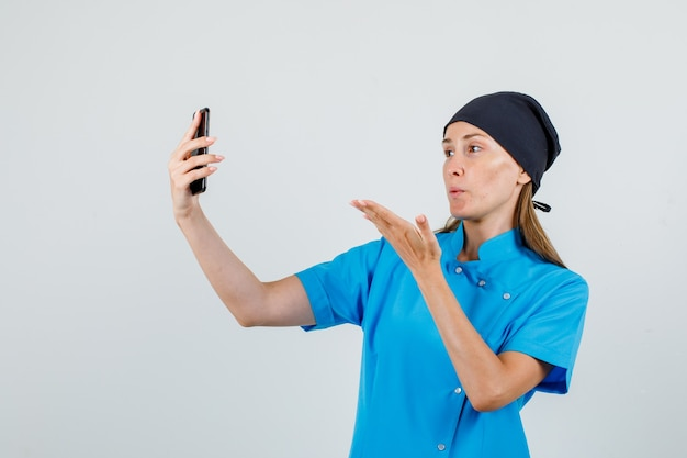 Kobieta lekarz wysyłający pocałunek podczas robienia selfie w niebieskim mundurze, czarnym kapeluszu
