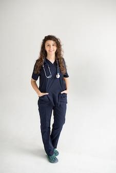 Kobieta lekarz z rękami w kieszeniach na białym, kopia przestrzeń