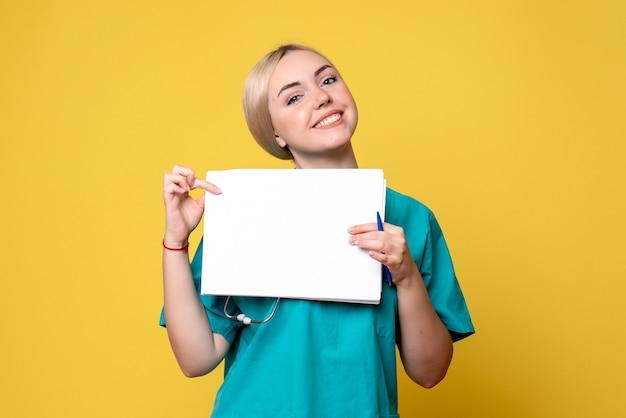 Kobieta lekarz z widokiem z przodu trzymająca różne dokumenty, pielęgniarka medyczna w szpitalu pandemicznym wirusa covid-19