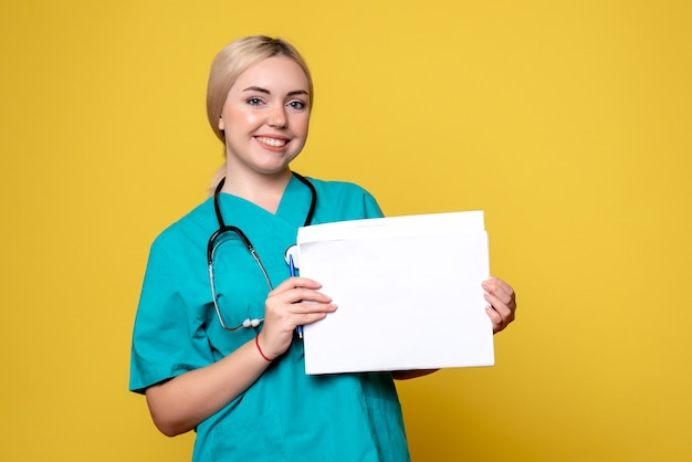 Kobieta lekarz z widokiem z przodu trzymająca różne dokumenty, wirus pandemii zdrowia covid-19 pielęgniarki szpitalnej