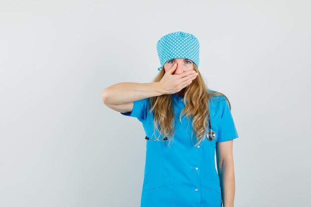 Kobieta lekarz zakrywający usta ręką w niebieskim mundurze i patrząc zszokowany.