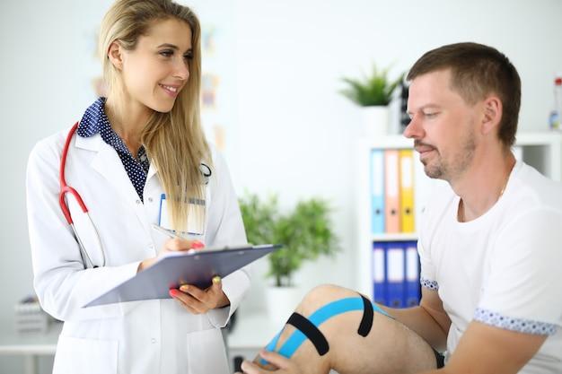 Kobieta lekarz zapisuje objawy pacjenta w schowku