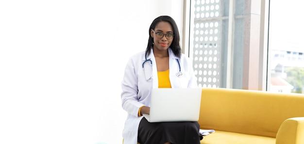 Kobieta lekarz zawód i koncepcja opieki zdrowotnej. african american kobieta lekarz siedzi na żółtej kanapie i białym tle