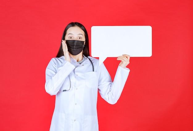 Kobieta lekarz ze stetoskopem i czarną maską trzyma prostokątne biurko informacyjne i wygląda na zdezorientowanego i zamyślonego.