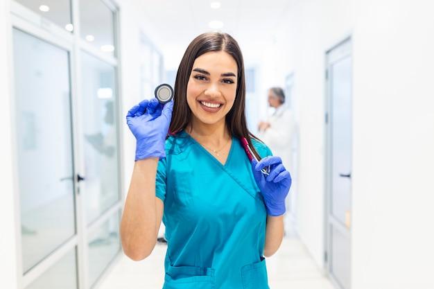 Kobieta lekarz ze stetoskopem w ręku i pacjenci przychodzą na tle szpitala.