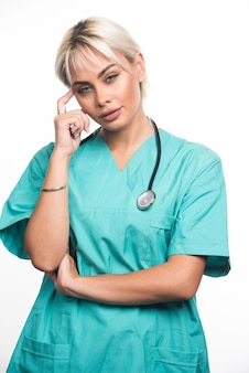Kobieta lekarz ze stetoskopem wskazującym palcem na głowę na białej powierzchni