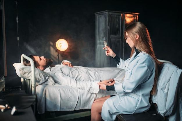 Kobieta lekarz ze strzykawką przeciwko pacjentowi płci męskiej
