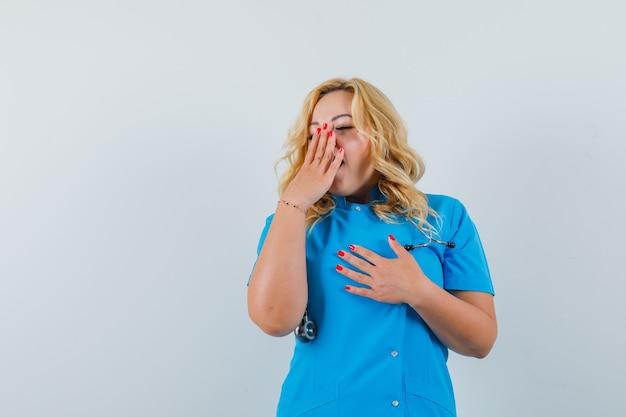 Kobieta lekarz ziewanie ręką na ustach w niebieskim mundurze i patrząc senne miejsce na tekst