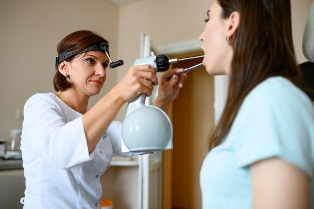 Kobieta lekarza i pacjenta w biurze, egzamin. badanie gardła w poradni, profesjonalna diagnostyka. lekarz specjalista i kobieta w szpitalu, laryngolog