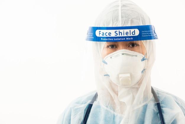 Kobieta lekarza personelu medycznego w mundurze śoi z maską ochronną i plastikową osłoną twarzy