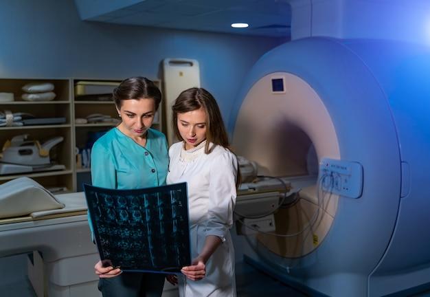 Kobieta lekarze omawiają prześwietlenie w nowoczesnej sali medycznej z tomografią komputerową.