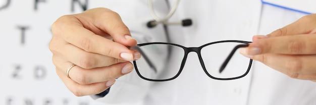 Kobieta lekarze ręce trzymają nowe stylowe okulary w optyce zbliżenie wybór okularów do pracy