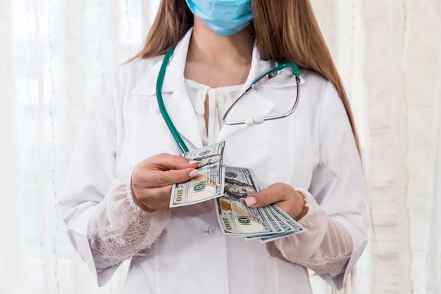 Kobieta lekarzy ręce liczenia banknotów dolara, łapówka