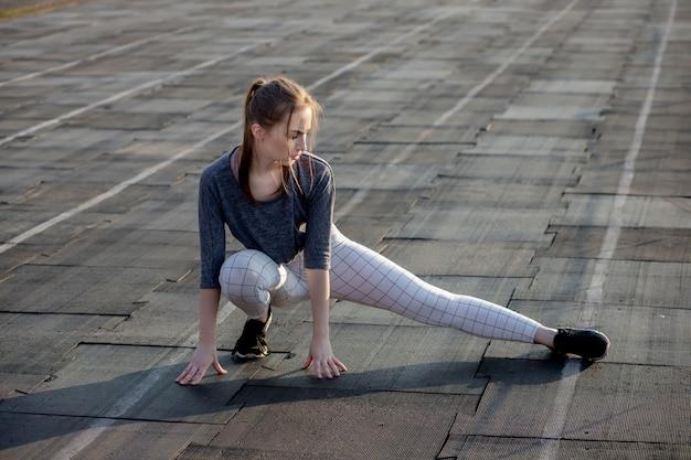 Kobieta lekkoatletka rozciąganie nogi na bieżni